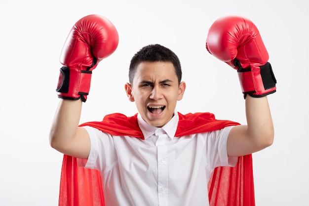 Zelfverzekerde jonge superheld jongen in rode cape doos handschoenen kijken camera verhogen vuisten schreeuwen geïsoleerd op een witte achtergrond