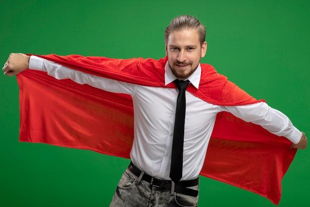 Zelfverzekerde jonge superheld kerel camera kijken en pakte mantel geïsoleerd op groene achtergrond