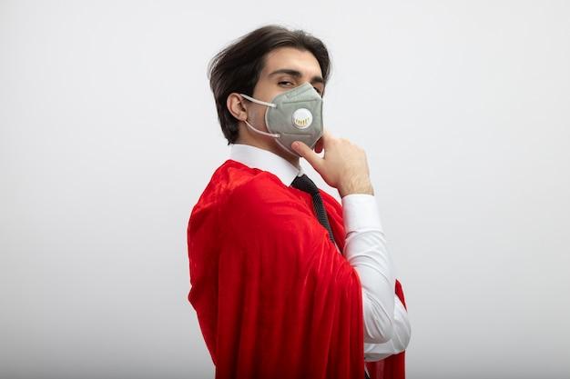 Zelfverzekerde jonge superheld man kijken camera dragen stropdas en medische masker hand op kin zetten