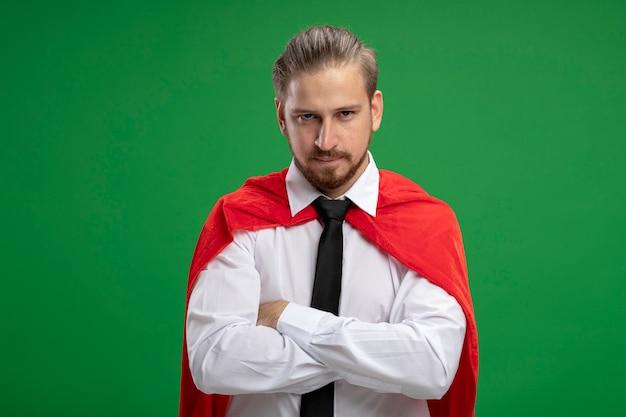 Zelfverzekerde jonge superheld man kijken camera kruising handen geïsoleerd op groene achtergrond
