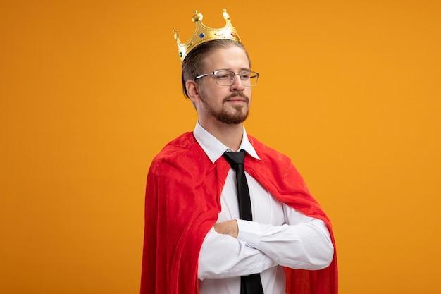 Zelfverzekerde jonge superheld man kijken kant dragen stropdas en kroon met bril handen geïsoleerd op een oranje achtergrond kruisen