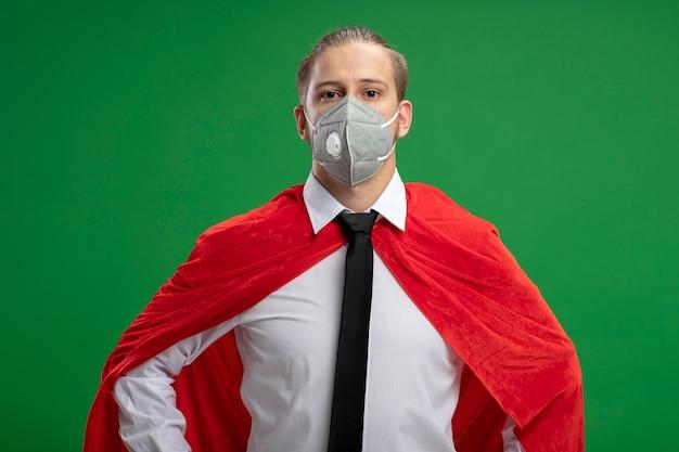 Zelfverzekerde jonge superheld man met medische masker en stropdas kijken camera geïsoleerd op groene achtergrond
