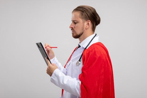 Zelfverzekerde jonge superheld man staande in profiel pose dragen medische mantel met een stethoscoop schrijven iets geïsoleerd op een witte achtergrond