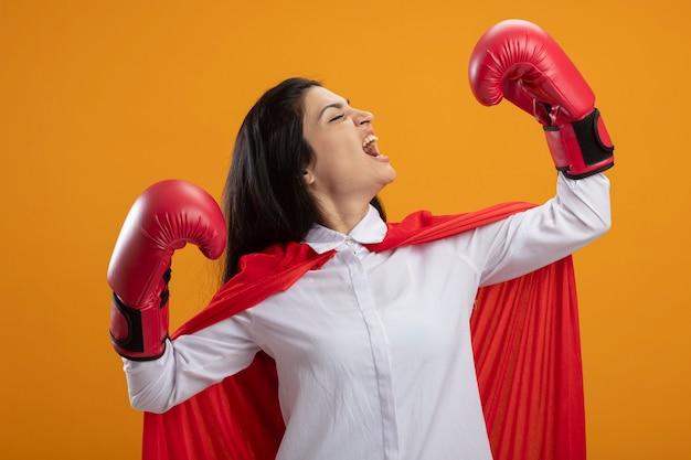 Zelfverzekerde jonge supervrouw die dooshandschoenen draagt die sterk gebaar doet die hoofd naar zij draait en schreeuwt met gesloten ogen die op oranje muur worden geïsoleerd