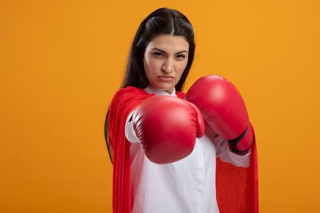 Zelfverzekerde jonge supervrouw die dooshandschoenen draagt die voorzijde bekijkt die boksgebaar doet dat op oranje muur wordt geïsoleerd