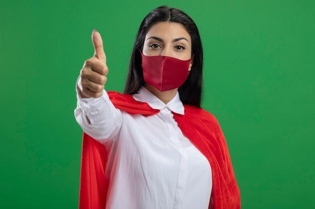 Zelfverzekerde jonge supervrouw die masker draagt dat voorzijde toont die duim toont die omhoog op groene muur wordt geïsoleerd