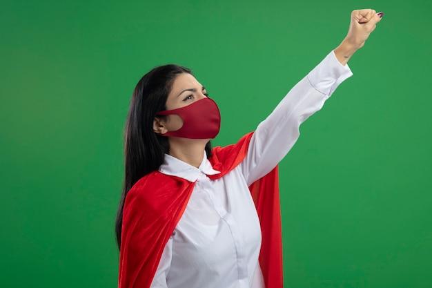 Zelfverzekerde jonge supervrouw die masker draagt dat zich in profielmening bevindt die haar vuist opheft als superman die omhoog geïsoleerd op muur kijkt