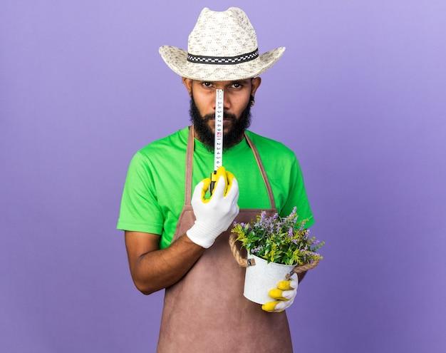 Zelfverzekerde jonge tuinman afro-amerikaanse man met bloem in bloempot met meetlint
