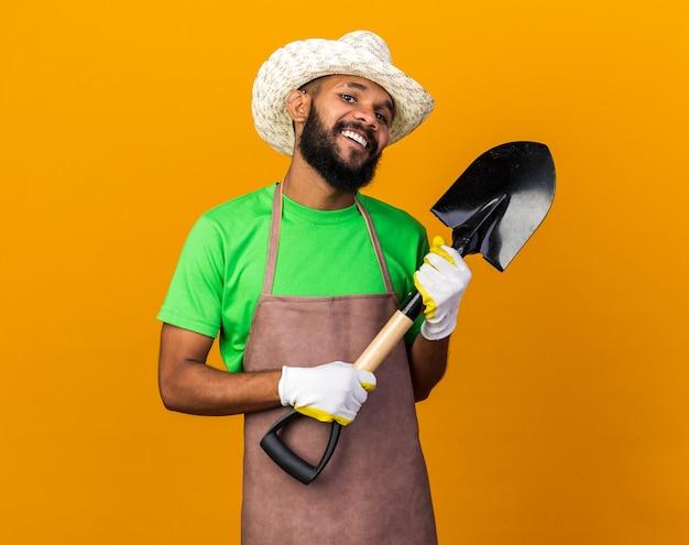 Zelfverzekerde jonge tuinman afro-amerikaanse man met tuinhoed en handschoenen met schop Gratis Foto