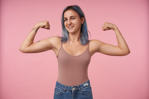 Zelfverzekerde jonge vrij kortharige vrouw met tatoeages die haar handen omhoog houden terwijl ze haar kracht demonstreert en er sluw uitziet, geïsoleerd op roze