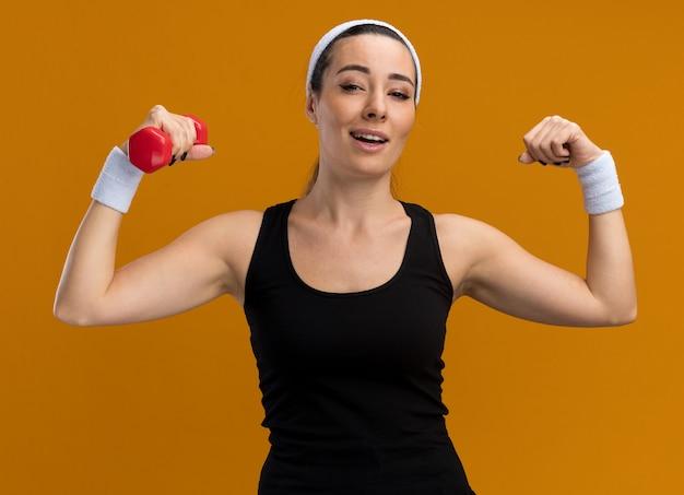 Zelfverzekerde jonge vrij sportieve vrouw met hoofdband en polsbandjes met halter die naar de voorkant kijkt en een sterk gebaar doet dat op een oranje muur wordt geïsoleerd