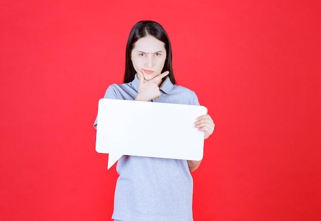 Zelfverzekerde jonge vrouw met wit bord