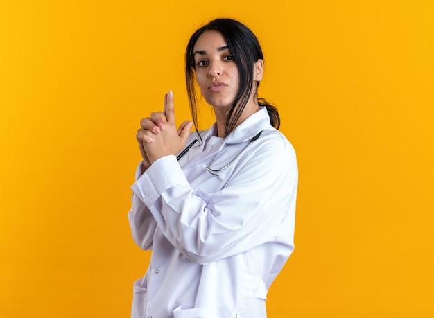Zelfverzekerde jonge vrouwelijke arts die een medisch gewaad draagt met een stethoscoop die een pistoolgebaar toont dat op een gele muur wordt geïsoleerd