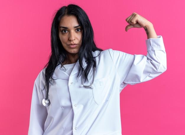 Zelfverzekerde jonge vrouwelijke arts die een medisch gewaad draagt met een stethoscoop die een sterk gebaar toont dat op een roze muur is geïsoleerd