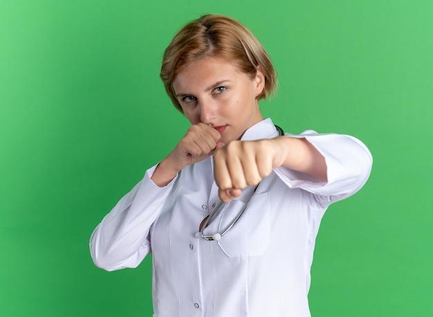 Zelfverzekerde jonge vrouwelijke arts die een medisch gewaad draagt met een stethoscoop die staat in de strijd, geïsoleerd op een groene muur
