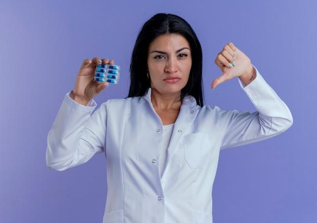Zelfverzekerde jonge vrouwelijke arts die het medische pak van de gewaadholding medische capsules draagt die het tonen van duim naar beneden kijken