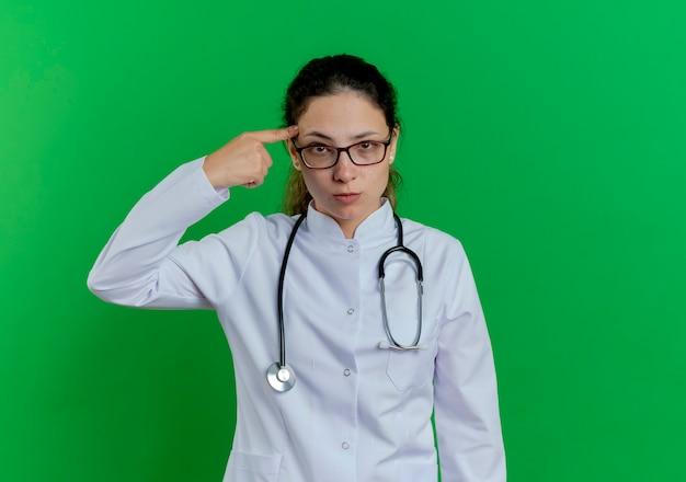 Zelfverzekerde jonge vrouwelijke arts die medische mantel en stethoscoop en bril draagt die vinger op hoofd richt dat op groene muur met exemplaarruimte wordt geïsoleerd