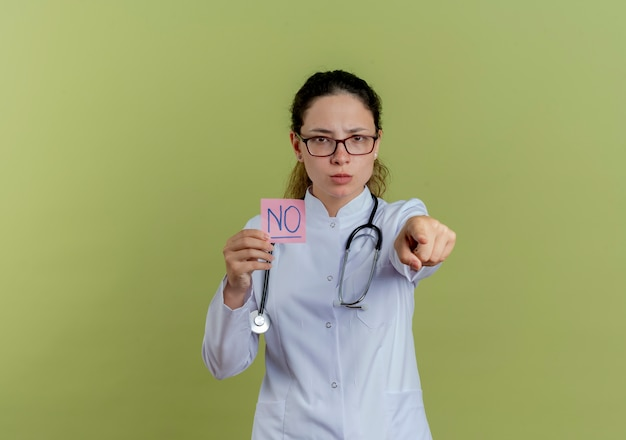 Zelfverzekerde jonge vrouwelijke arts die medische mantel en stethoscoop met bril draagt die document notapunten geïsoleerd houdt