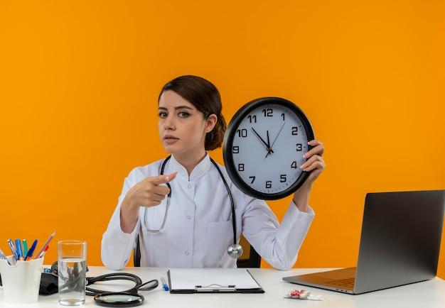 Zelfverzekerde jonge vrouwelijke arts die medische mantel en stethoscoopzitting aan bureau met medische hulpmiddelen en laptop holdingsklok wijst geïsoleerd op gele muur