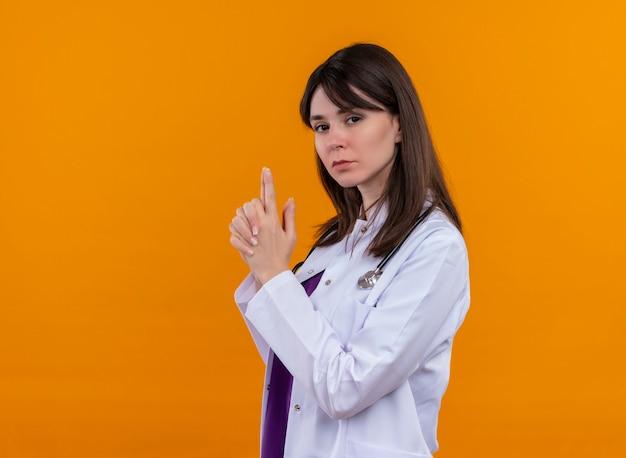 Zelfverzekerde jonge vrouwelijke arts in medische mantel met stethoscoop gebaren pistool met beide handen op geïsoleerde oranje achtergrond met kopie ruimte
