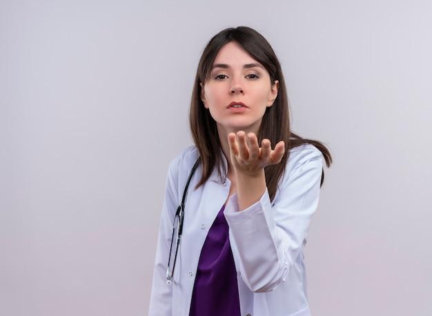 Zelfverzekerde jonge vrouwelijke arts in medische mantel met stethoscoop houdt hand open en kijkt naar camera op geïsoleerde witte achtergrond met kopie ruimte