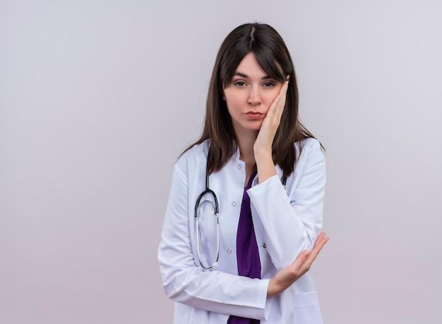 Zelfverzekerde jonge vrouwelijke arts in medische mantel met stethoscoop legt hand op kin op geïsoleerde witte achtergrond met kopie ruimte