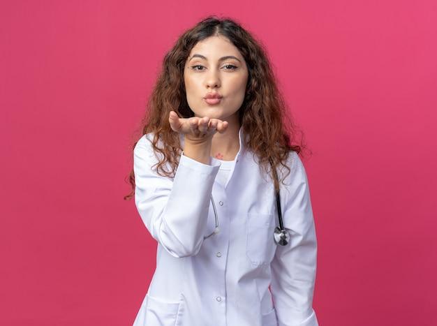 Zelfverzekerde jonge vrouwelijke arts met een medisch gewaad en een stethoscoop die een klapkus stuurt die op een roze muur met kopieerruimte wordt geïsoleerd
