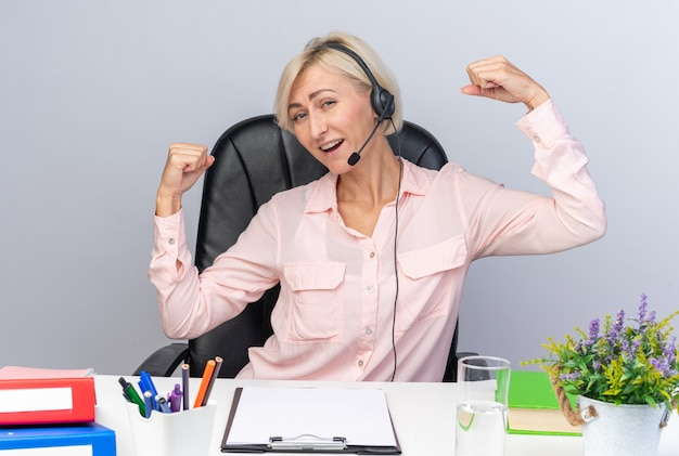 Zelfverzekerde jonge vrouwelijke callcentermedewerker die een headset draagt die aan tafel zit met kantoorhulpmiddelen die een sterk gebaar doen dat op een witte muur wordt geïsoleerd