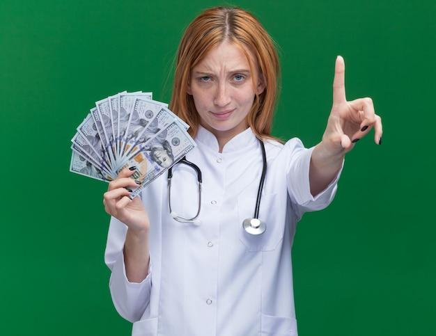 Zelfverzekerde jonge vrouwelijke gemberdokter met een medisch gewaad en een stethoscoop die geld vasthoudt en een gebaar vasthoudt dat op een groene muur is geïsoleerd