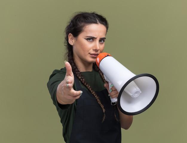 Zelfverzekerde jonge vrouwelijke kapper in uniform spreekt op luidspreker en toont je gebaar geïsoleerd op olijfgroene muur