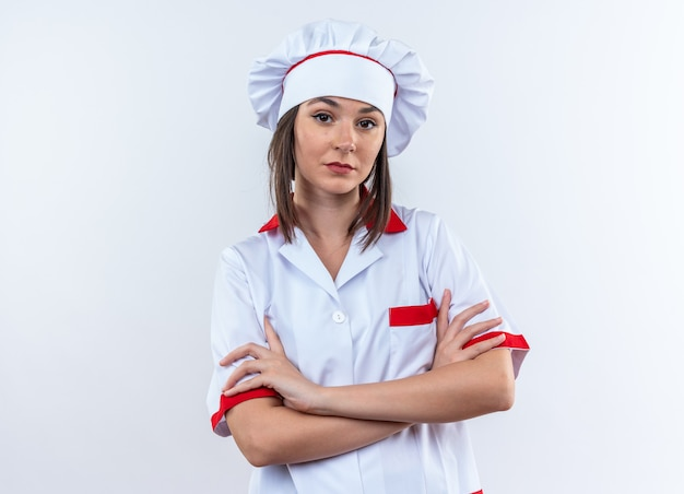 Zelfverzekerde jonge vrouwelijke kok die chef-kok uniform draagt die handen kruist die op witte achtergrond worden geïsoleerd