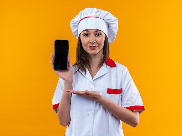 Zelfverzekerde jonge vrouwelijke kok die een chef-kok uniform draagt en wijst met de hand naar de telefoon geïsoleerd op een oranje muur
