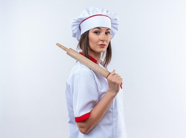 Zelfverzekerde jonge vrouwelijke kok die een chef-kok uniform draagt met deegroller op de schouder geïsoleerd op een witte muur