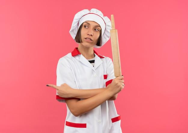 Zelfverzekerde jonge vrouwelijke kok in chef-kok uniforme deegroller houden en kijken en wijzen naar kant geïsoleerd op roze met kopie ruimte