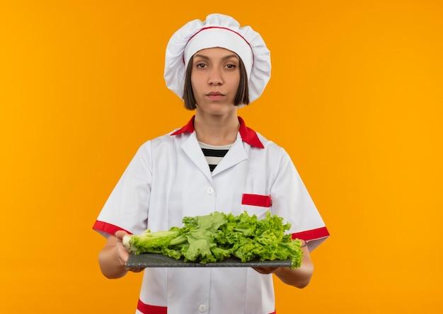 Zelfverzekerde jonge vrouwelijke kok in chef-kok uniforme snijplank met sla erop houden en geïsoleerd op oranje met kopie ruimte kijken