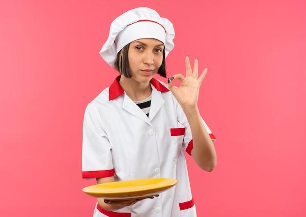 Zelfverzekerde jonge vrouwelijke kok in eenvormige chef-kok die lege plaat houdt en ok teken doet dat op roze met exemplaarruimte wordt geïsoleerd