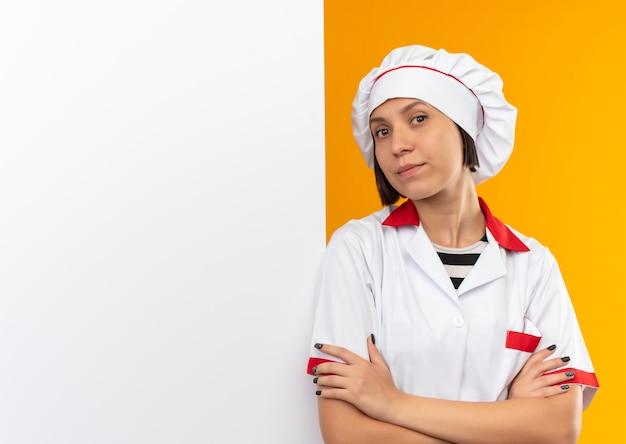 Zelfverzekerde jonge vrouwelijke kok in eenvormige chef-kok die zich met gesloten houding voor witte muur bevindt die op oranje met exemplaarruimte wordt geïsoleerd