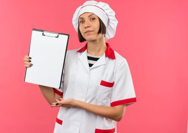 Zelfverzekerde jonge vrouwelijke kok in uniform chef-kok tonen en met de hand wijzend op klembord geïsoleerd op roze met kopie ruimte