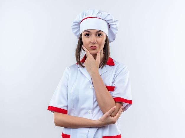 Zelfverzekerde jonge vrouwelijke kok in uniform van de chef-kok die de hand op de kin legt die op een witte muur wordt geïsoleerd