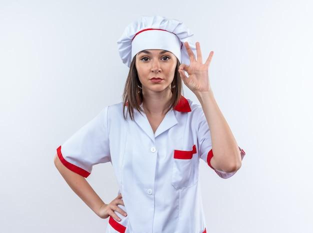 Zelfverzekerde jonge vrouwelijke kok in uniform van de chef-kok die een goed gebaar toont dat op een witte achtergrond wordt geïsoleerd Gratis Foto