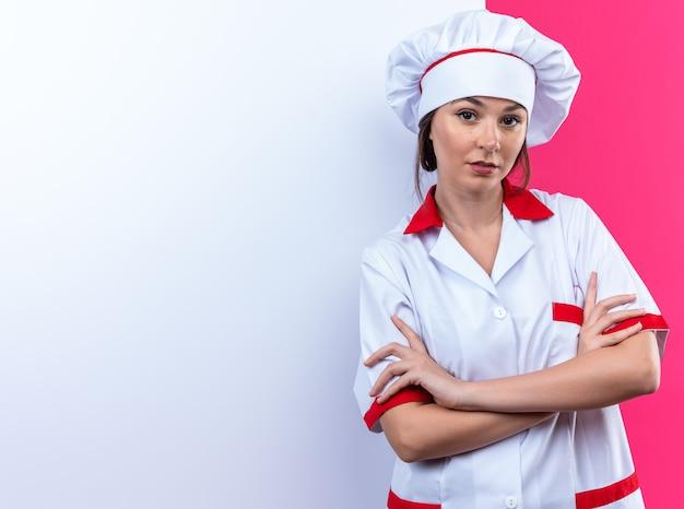 Zelfverzekerde jonge vrouwelijke kok in uniform van de chef-kok die voor de witte muur staat en de hand kruist geïsoleerd op een roze achtergrond met kopieerruimte