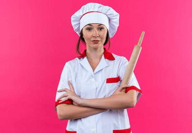 Zelfverzekerde jonge vrouwelijke kok in uniform van de chef-kok met deegroller die handen kruist geïsoleerd op roze muur