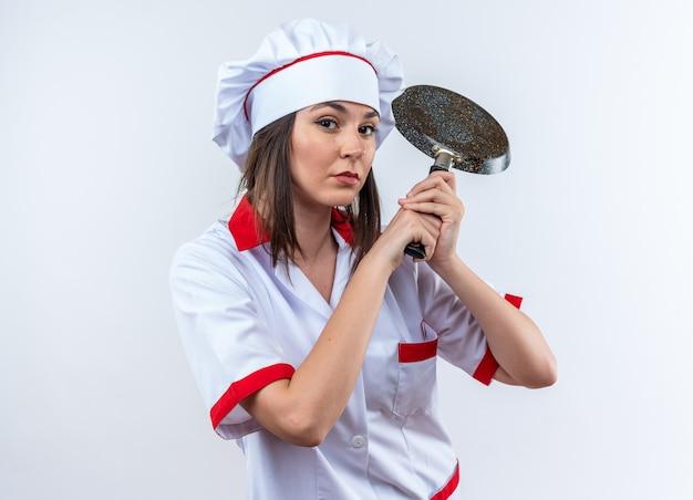 Zelfverzekerde jonge vrouwelijke kok met een uniform van de chef-kok die een koekenpan houdt die op een witte achtergrond wordt geïsoleerd