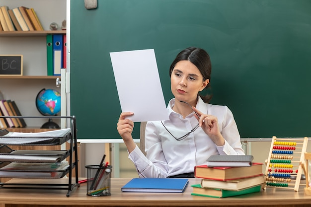 Zelfverzekerde jonge vrouwelijke leraar die papier vasthoudt met een bril die aan tafel zit met schoolhulpmiddelen in de klas