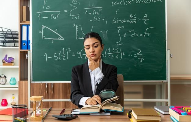 Zelfverzekerde jonge vrouwelijke leraar zit aan tafel met schoolhulpmiddelen, leesboek met vergrootglas, greep de kin in de klas