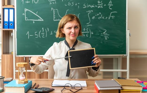 Zelfverzekerde jonge vrouwelijke leraar zit aan tafel met schoolhulpmiddelen op mini-bord met aanwijzer in de klas