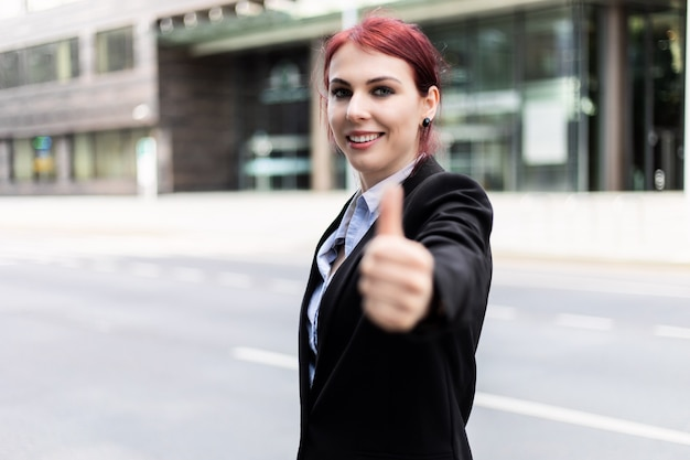 Zelfverzekerde jonge vrouwelijke manager buiten in een moderne stedelijke omgeving met duimen omhoog
