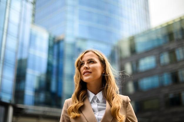Zelfverzekerde jonge vrouwelijke manager buiten in een moderne stedelijke omgeving. veel copyspace
