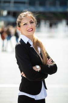 Zelfverzekerde jonge vrouwelijke manager buiten in een moderne stedelijke omgeving