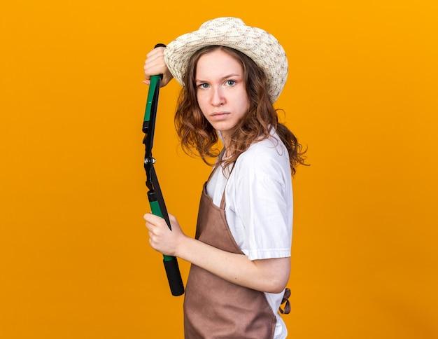 Zelfverzekerde jonge vrouwelijke tuinman met een tuinhoed met een snoeischaar geïsoleerd op een oranje muur